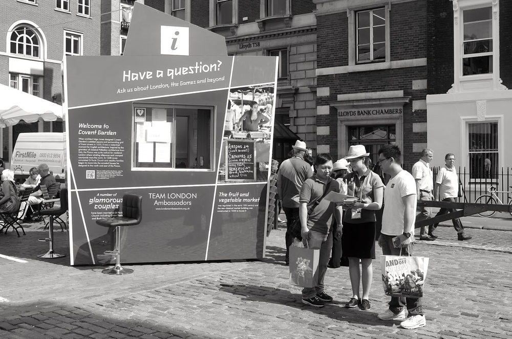 Any questions, please, in a multitude of languages. This information point is on the edge of Covent Garden, a few yards from Apple's flagship store. Covent Garden is the former industrialised fruit and vegetable market but has now become a place to shop, relax and eat