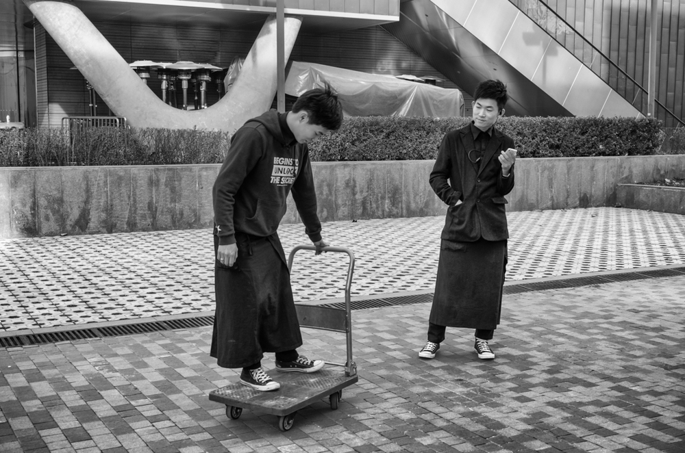 Off-duty waiters indulge in a spot of cart-boarding in Beijing's Sanlitun