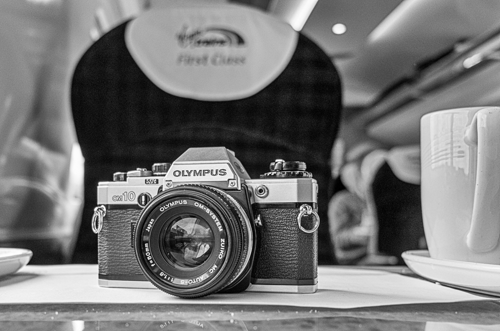 My bargain-basement Olympus OM10 and f/1.8 50mm Zuiko lens on its way back to London on Virgin's finest Pendalino: Perfect condition for under £50 and an ideal way to get back into film photography at little cost (Photo: Leica X Vario)