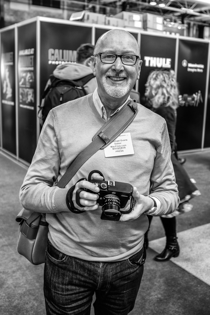 It's a hard life reporting on any exhibition: The author, Google Glassless, with his Leica M (possibly the only Leica in the halls at the time) and 35mm Summilux FLE. Note, no need for 400mm telephoto. (Photo Fuji X100S (ISO 200)