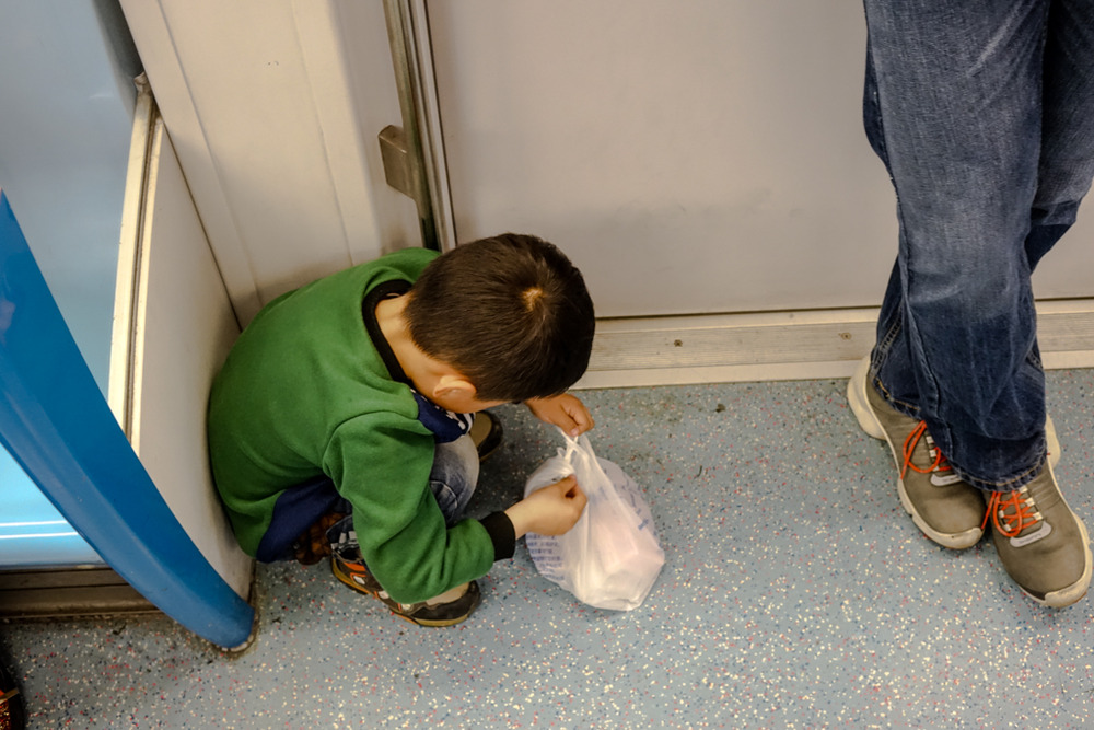 Metro trains are invariably crowded but this little chap managed to find himself his own tiny space, happily playing with the plastic bag. What was inside? Condoms!