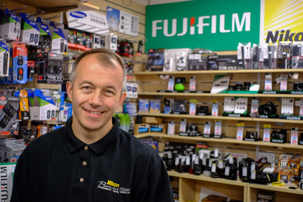 Andy at Chiswick Camera Centre. Above, Fuji X-T1 with Leica 28mm f/2.8 Elmarit. Below, Same camera, this time with the Fujinon f/2.8 27mm pancake. Both shots at f/2.8 and 1/125s, full-frame equivalent of 41mm.