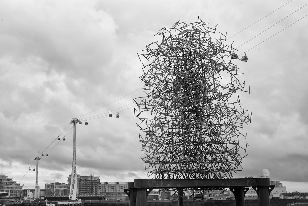 Antony Gormley's impressive Quantum Cloud sculpture sitting in the Thames beside the O2 Millennium Dome. Note the illusionary human figure resembling a latter-day Wickerman sacrifice. Above it snakes the Emirates Air Line cablecar which carries passengers from the O2 to the north bank of the Thames at Custom House in Docklands. This is actually a part of London's public transport system, even used by a few commuters. Photo Mike Evans