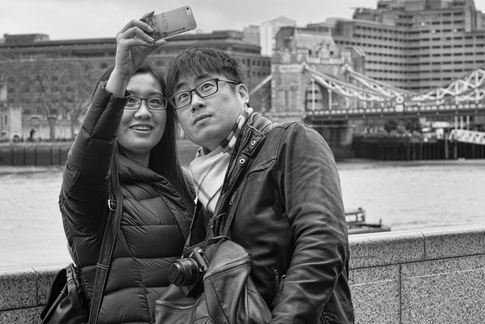 Never miss a selvesie in front of Tower Bridge: In this case the far more competent Sony RX1 was left neck dangling while the versatile iPhone was pressed into service. Judging from the phone cover, these two trophy hunters have just arrived from the Eiffel Tower and want to add to their collection.  Photo Mike Evans.