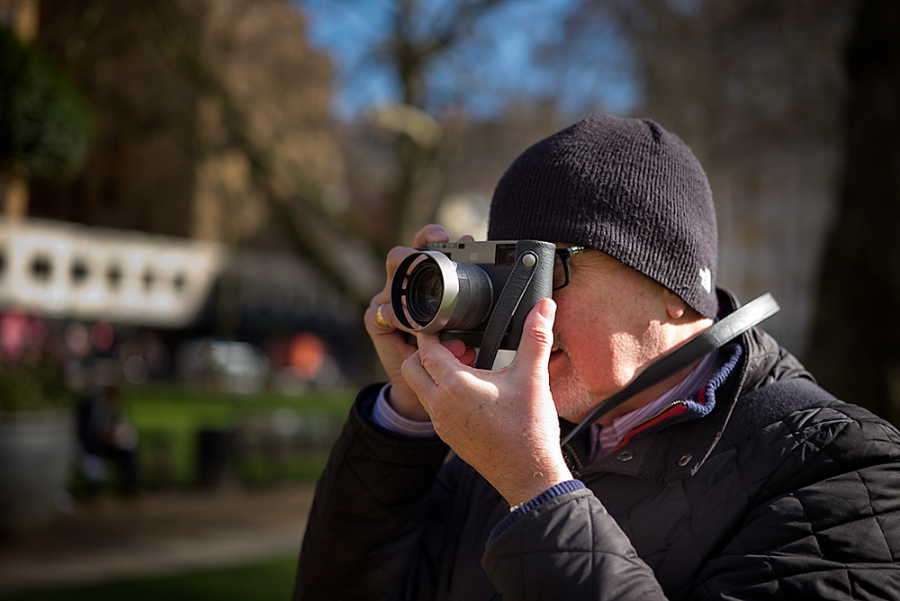 The M60 sings in Berkeley Square: This beautiful camera comes with a fine leather case and neck strap as you can see here. Since there are no strap lugs on the body, use of the Leica-designed case is mandatory (Picture of Editor Evans in action on a chilly day, taken by George James, Leica M-P with 50mm Apo-Summicron-M ASPH)