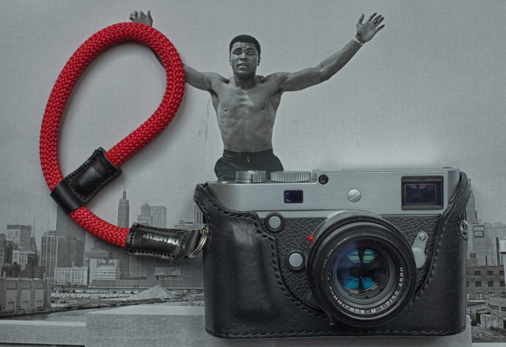 The wrist strap looks good on this Leica M-P and 50 Apo with one of Sejun Kim's superb Arte di Mano half cases from Korea. Background: Thomas Hoepker's iconic picture of Muhammad Ali from the June page of this year's Leica calendar