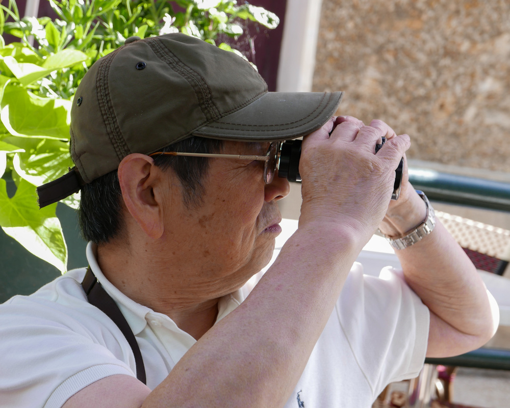 Noted Japanese collector and author, Shinichi Nakamura tries out a pair of old Zeiss binoculars which Peter Loy had just snapped up at a bargain price