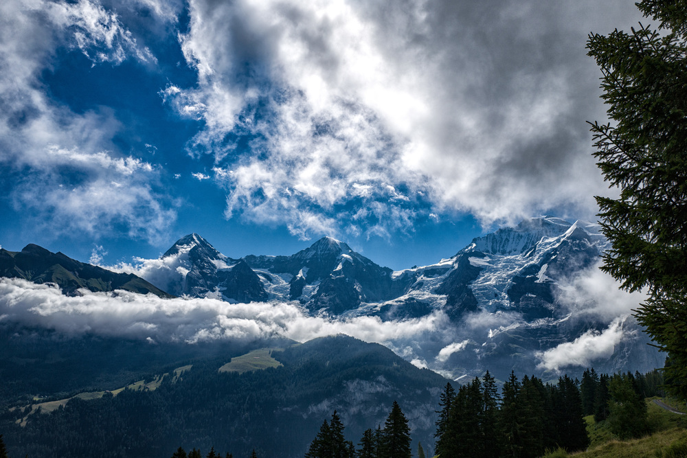 The three strong men of the Bernese Oberland—Eiger, Mönch and Jungfrau (partly hidden by clouds). See the Jungfraujoch buildings in the saddle between Mönch and Jungfrau. This is Europe's highest railway station. This shot taken from near Winteregg on the Grütschalp-Mürren path on the opposite side of the Lauterbrunnental