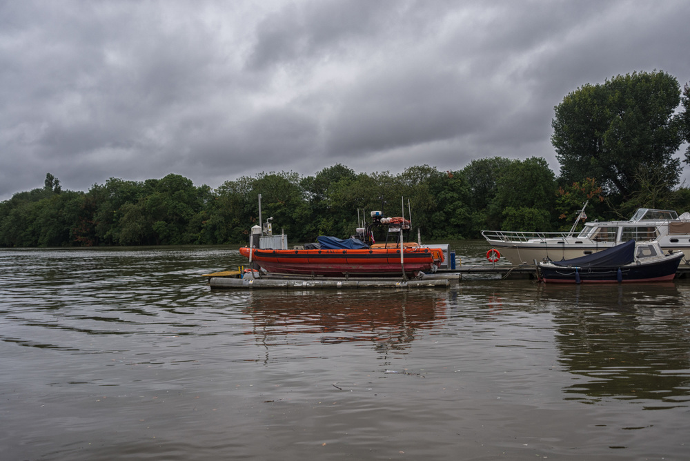 Chiswick life boat rides high as the Thames tide approaches record levels. On calmer and less gloomy days, as below, the Royal National Lifeboat Institute rescue vessel rides low on its moorings. Note the top of the pole almost level with the boat in the above picture