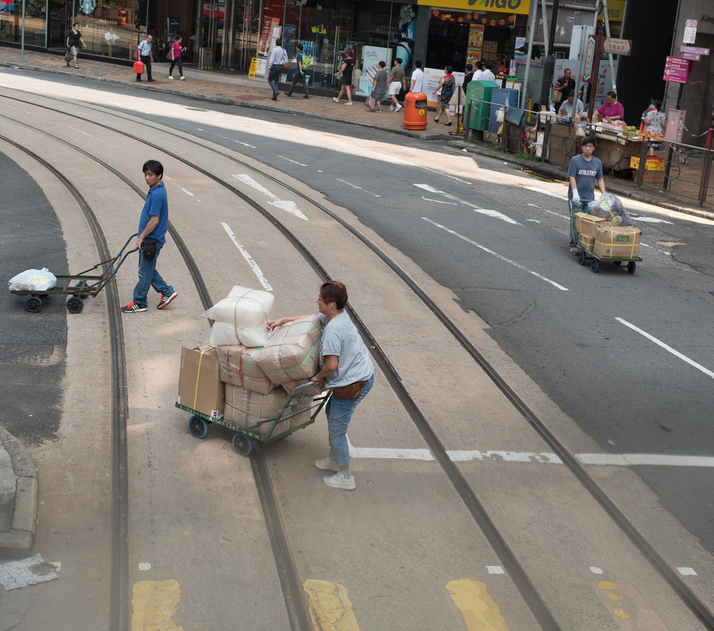 It is absolutely obligatory to get a picture of a man pushing a cart across a busy junction. All visitors to Hong Kong know this. So I've got it out of the way and provided a bonus: Two men and one woman pushing three carts across the tram tracks