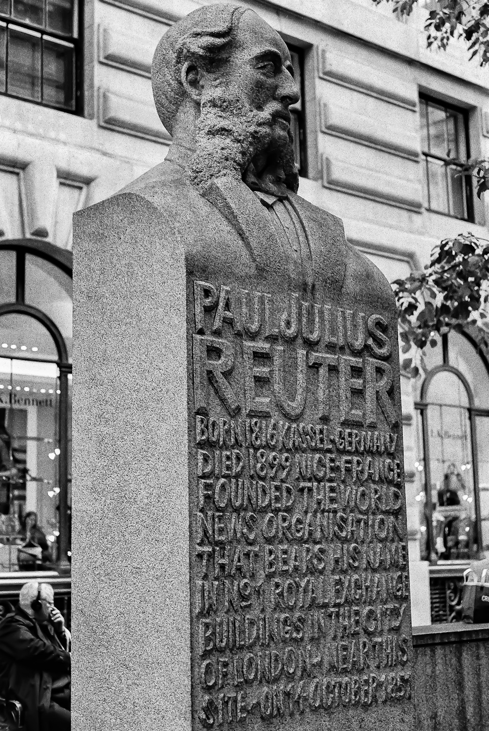 Paul Julius Reuter, father of news gathering, fittingly stands sentinel outside Leica's new store in the City of London. Taken with my M4-P and late-model f/2.8 Elmar on Tri-X. Note that the statue itself has a stone surface with more grain than the Kodak film.