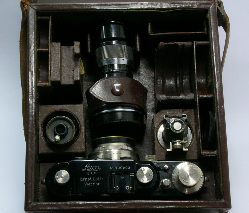 This kit includes the camera and 50mm lens, a further 105mm lens, a universal viewfinder, film cassette and filters. To the top left is an angular viewfinder would have sat and the lens slot to the right was intended for a 35mm lens--not present in this kit. It is an extremely compact way of carrying a full complement of photographic equipment. Note the near identical layout to the contemporary advertisement above.
