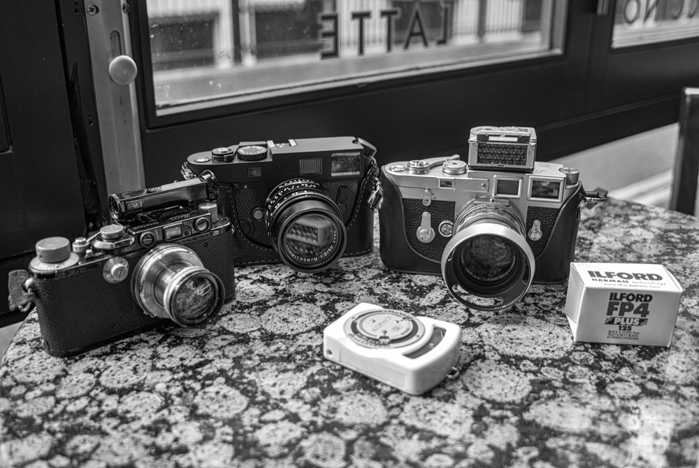On the starting grid: Three film cameras, one roll of film and two rather mad camera nerds. Left to right: Leica III and 5cm Summar, plus Winkelsucher (1936); Neil the M7 (2004) and 50mm Apo-Summicron; Leica M3 double-stroke (1957) with 50mm Summicron dual-range (with Sekonic light meter on top), Ilford FP4 and Adam's classic Ikophot light meter