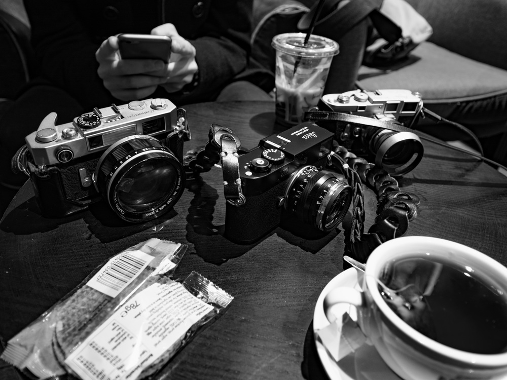Here's the scene when the Olympus had recovered its composure: Canon, Leica M-D and Sonnar, Leica M3 and 50mm DR Summicron. Tea and biscuits courtesy of Caffe Nero. (Photo Olympus)