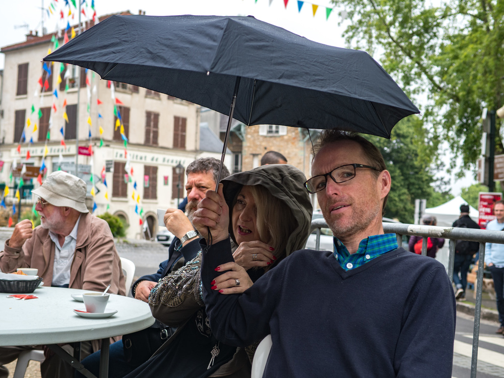 British dealer Peter Loy (right) shares an umbrella with Elaine Cooper of Red Dot Cameras. Ivor Cooper catches the drops next to Elaine