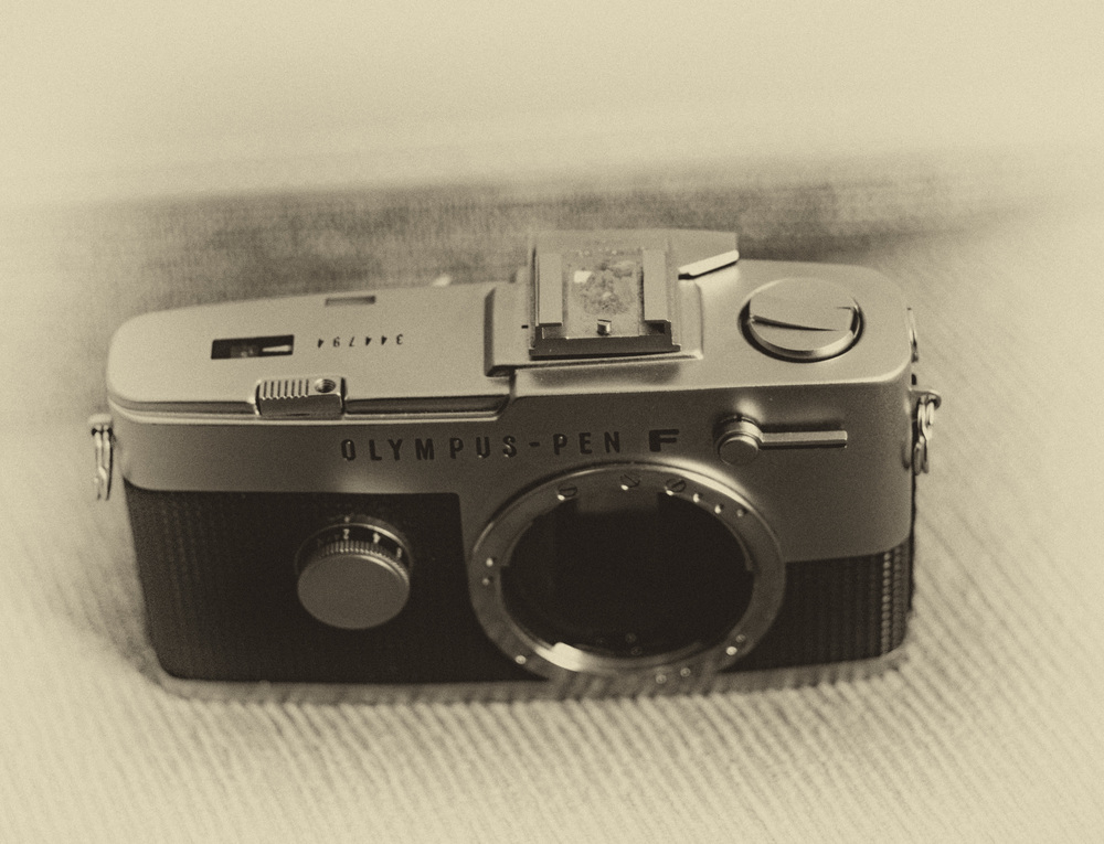 Olympus PEN-F from around 1966: A half-frame single-lens reflex built to a high standard. The accessory shoe is a slide-on device (compare with the photo below showing the camera without the shoe)