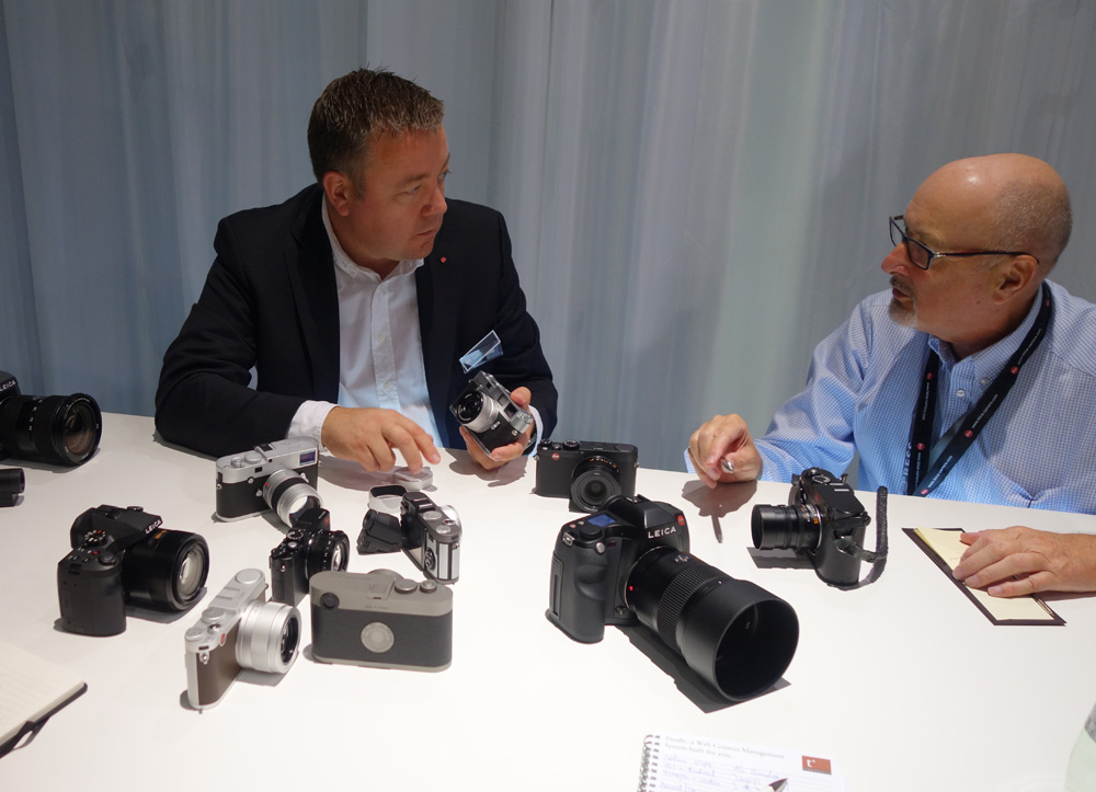 Photokina 2014 Candy Store: Mike gets the lowdown on the Leica newcomers from Product Manager, Stefan Daniel. (Photo: Dr. Michael Pritchard of the Royal Photographic Society).