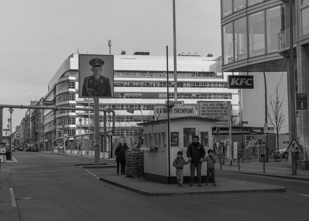 "Checkpoint Charlie pastiche 2017: This badly executed tourist ""attraction"" does nothing to convey the sense of foreboding that characterised return to the repressive East German regime. Charlie was the crossing point for vehicular traffic between west to east. In the centre of the road, behind the temporary utility bridge was the East German control area with tank traps and office buildings for processing of passports and visas. The hut in the centre acted as an allied guard post. I'm not now sure if it is the original or a reconstruction. Outside the picture, on the right, is the Haus am Checkpoint Charlie museum which has been there as long as I can remember"
