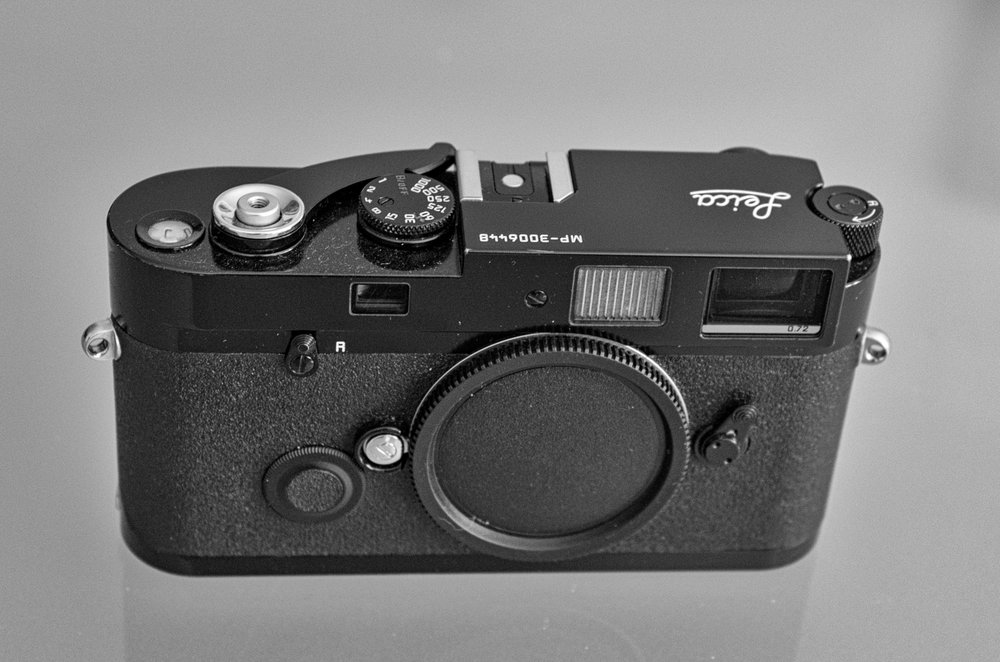 A modern black-paint MP film camera, this one manufactured in 2004 but still current in the catalogue. This is the more desirable MP, rather than the chrome version, and a similar model will sell for about £2,200. Even brassing, where the paint is rubbed   as a result of normal wear   to reveal the underlying brass (this camera has a little next to the strap lugs) will not be a problem since many collectors like it.
