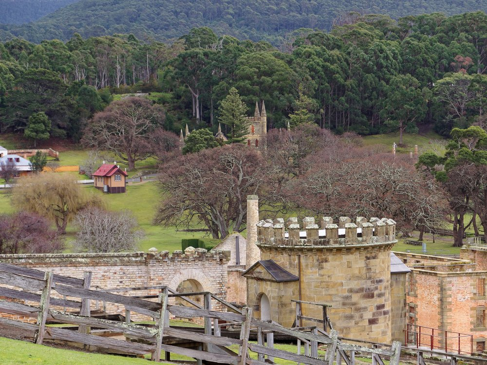 Looking across the Port Arthur Penal settlement. The original church spire ruins are glimpsed in the trees, the more recent St Davids Church (1927) in the clear ground to the left.  One of the more notorious convict destinations early in the Australian colony, it is remote, savaged by weather and strangely beautiful