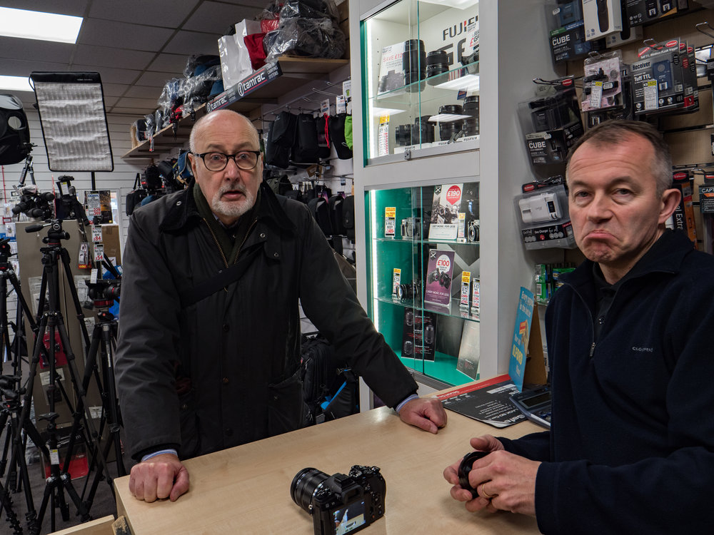 Enthusiasm unbridled: Andy Sands, right, isn't impressed with the G9 — but then he wouldn't be,  he's an Olympus dealer    —while Mike is under anaesthetic. The Olympus OM etc etc is on the counter, the G9 favouring the befuddled editor with its contrast-detect AF system