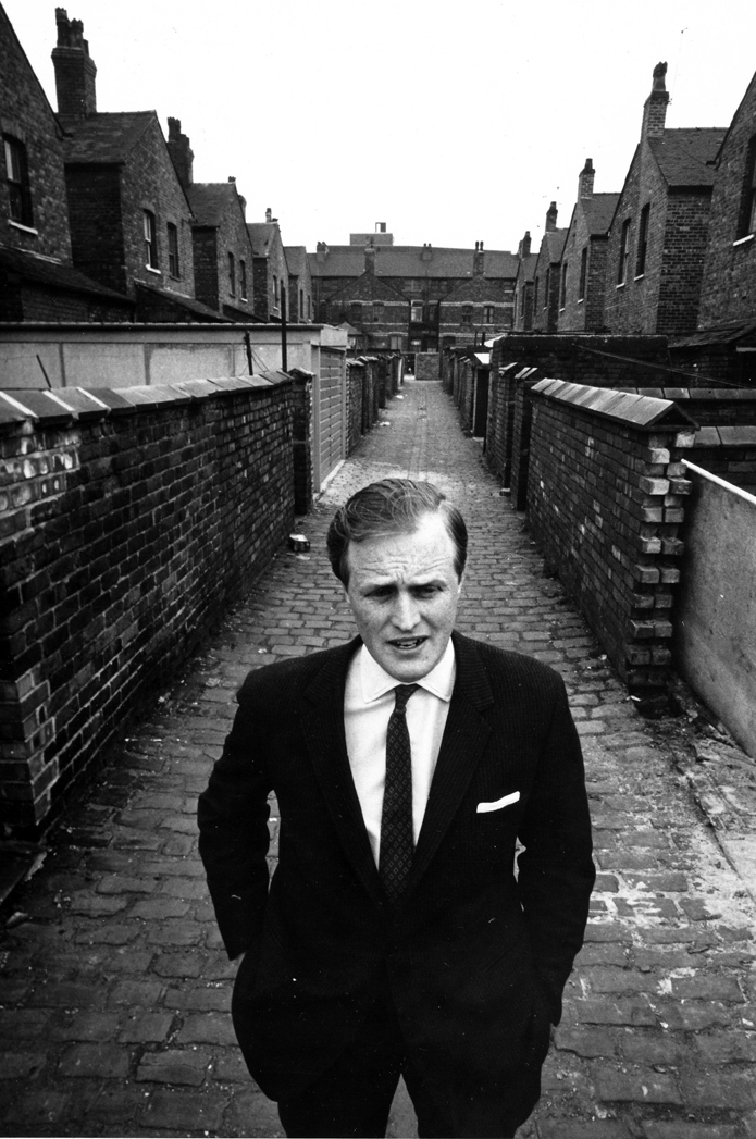 "Winston Spencer Churchill Jnr, the wartime leader's grandson, on the campaign trail in Stretford in the early 1970s. the ""back ginnell"" between the terraced houses is a standard feature of most northern towns and cities (image Don Morley)"