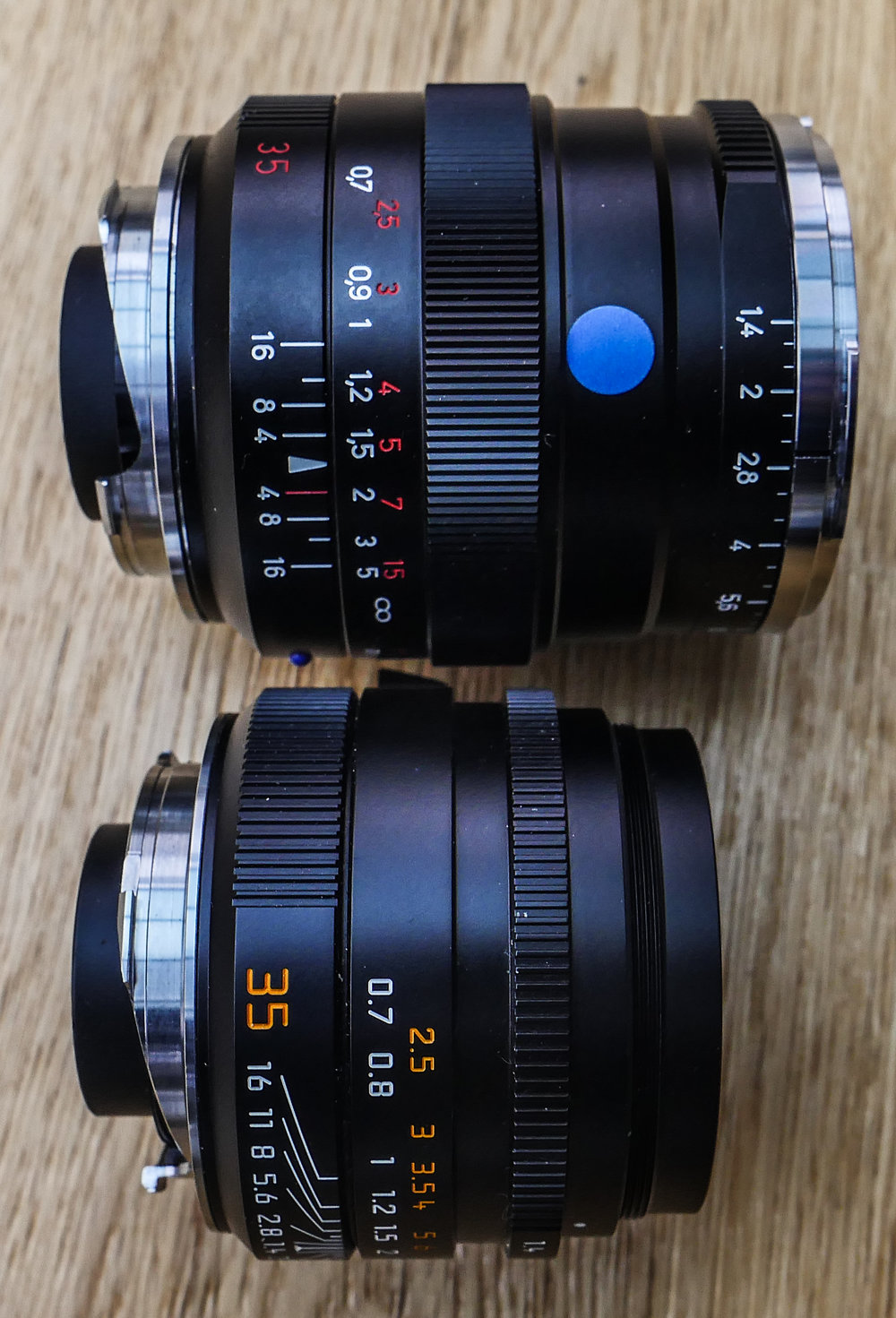 Design cues: The Zeiss is longer and heavier than the Leica. At first glance it looks more like the 50mm Summilux. Note the 1/3-stop aperture ring on the Distagon compared with the traditional 1/2-stop calibration of the Summilux (although not visible here). The large, ribbed focus ring on the Zeiss lens is much easier to grip than the smooth ring of the Leica. However, the large concave focus tab of the Summilux (hidden in this picture) is preferable to the small domed version on the Distagon. The (supplied) hood of the Summilux screws into the external thread seen above. The hood for the Distagon (not supplied) attaches to the chrome bayonet ring