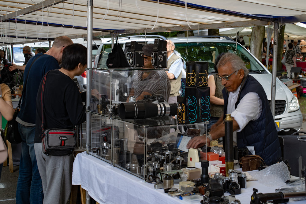 Setting up the stall — old and more recent cameras and lenses jockey for position.