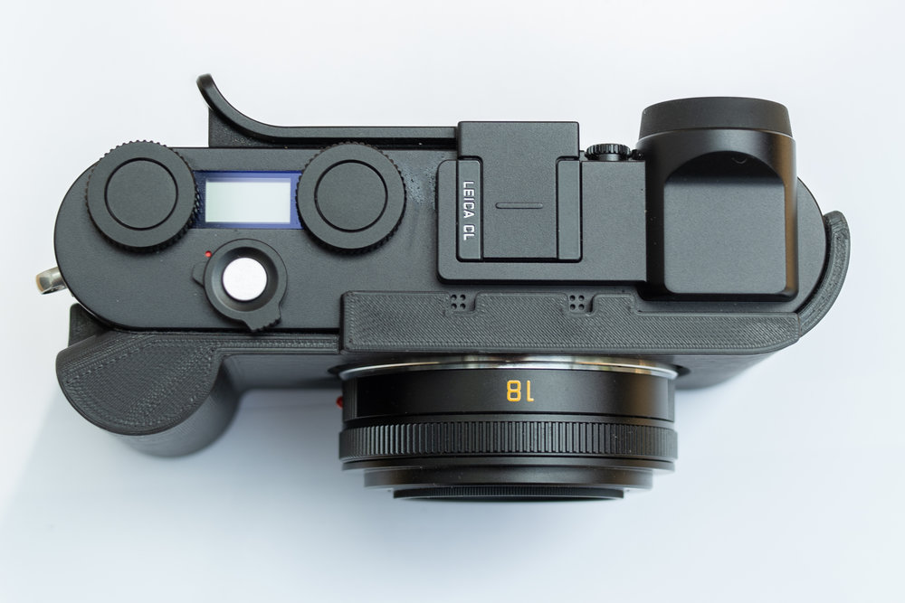 The case offers excellent protection for the camera and the grip is superior in use to the standard Leica Handgrip for the CL. Note the step above the lens (with microphone perforation) which adds to security and creates a uniform top level with the hot-shoe mount and the forward section of the electronic viewfinder