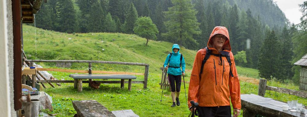 Hikers arriving in a rainstorm at Konjščica mountain cafe in Triglav National Park, Slovenia.