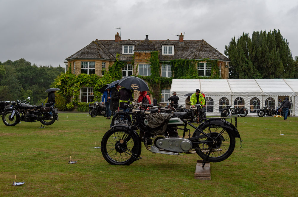 Middle Aston House    — a smart resort for well-heeled countryphiles — as a backdrop to the rained-off Brough Superior Club Diamond Jubilee. Note the lowering skies as they lowered by the minute. Centre-right, in the yellow jacket and woolly hat, is my friend Nick Jeffery, still looking for a parking place to exhibit his Brough