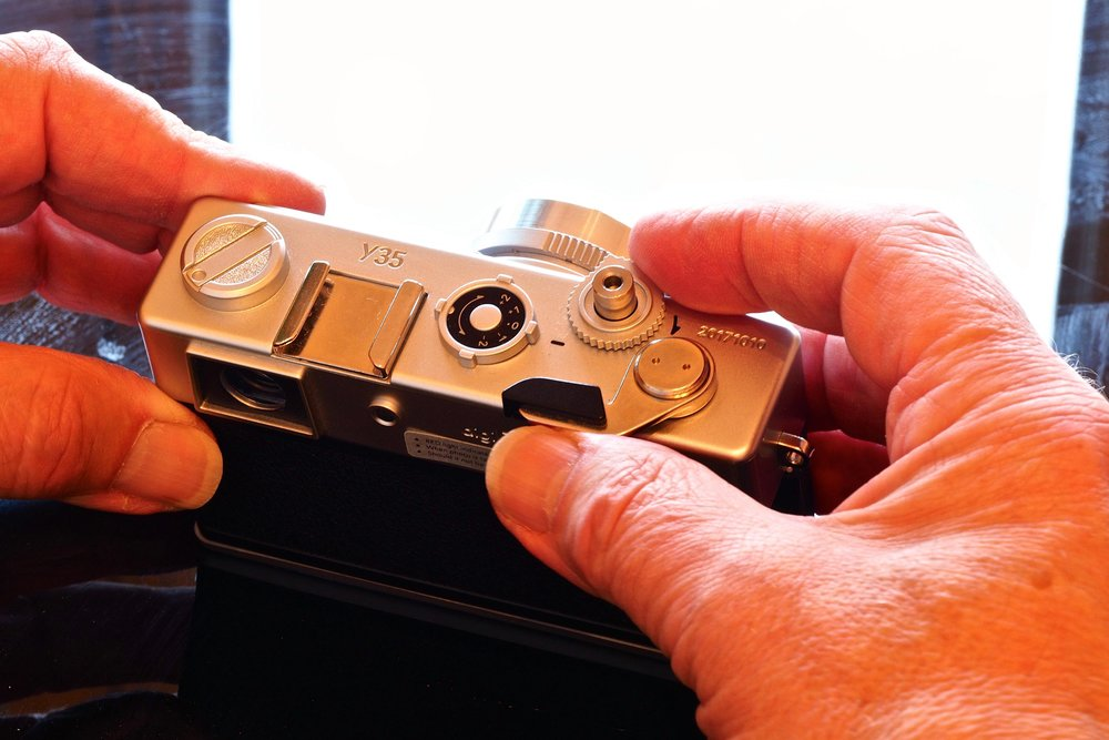 Plastic 'Yashica' Y35 14 megapixel camera with manual 'wind-on' shutter-interlock lever. Fixed focus, fixed aperture, auto-only shutter speeds, optical viewfinder, under- & over-exposure adjustment (by guesswork) lever on top, no screen.