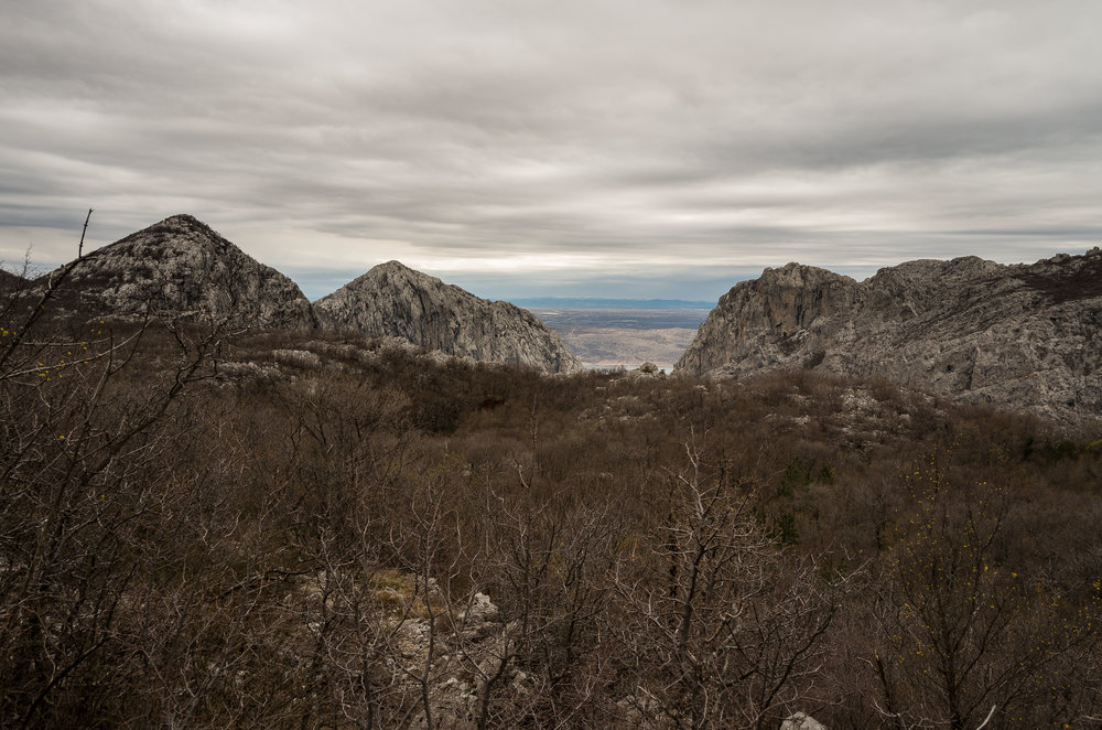 The rocky Grabove Doline plateau with the peaks of the gorge and sea beyond.