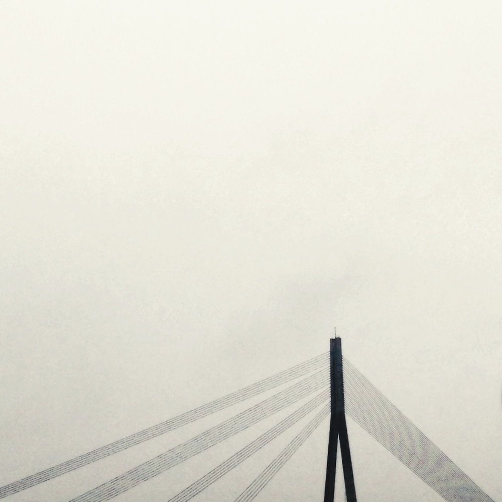 Vansu Bridge peeking through the cloud cover of Riga