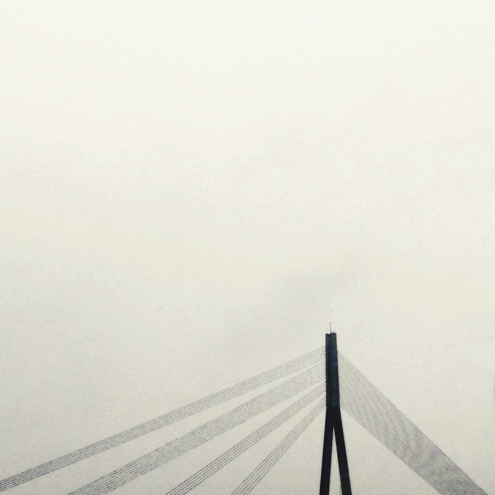 Vansu Bridge peeking through the cloud cover of Riga