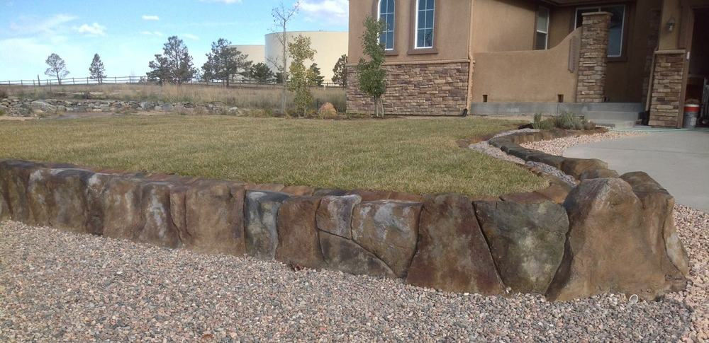 This Front Yard retaining wall is all one-piece of poured in place cement that we carved and stained to get the real rock look.
