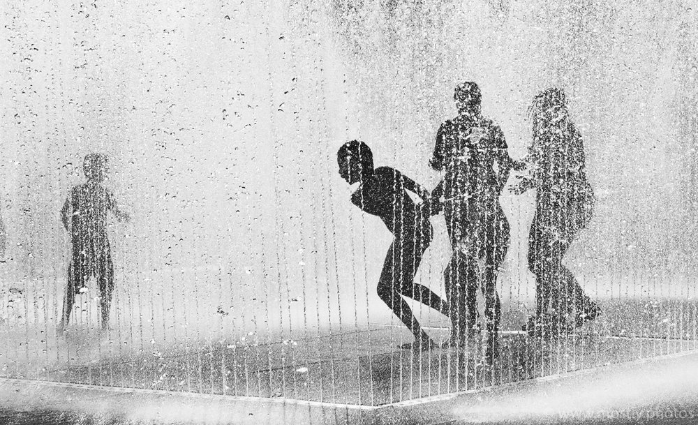 Silhouettes of people playing in the Fountains on Londons Southbank in the Summer.