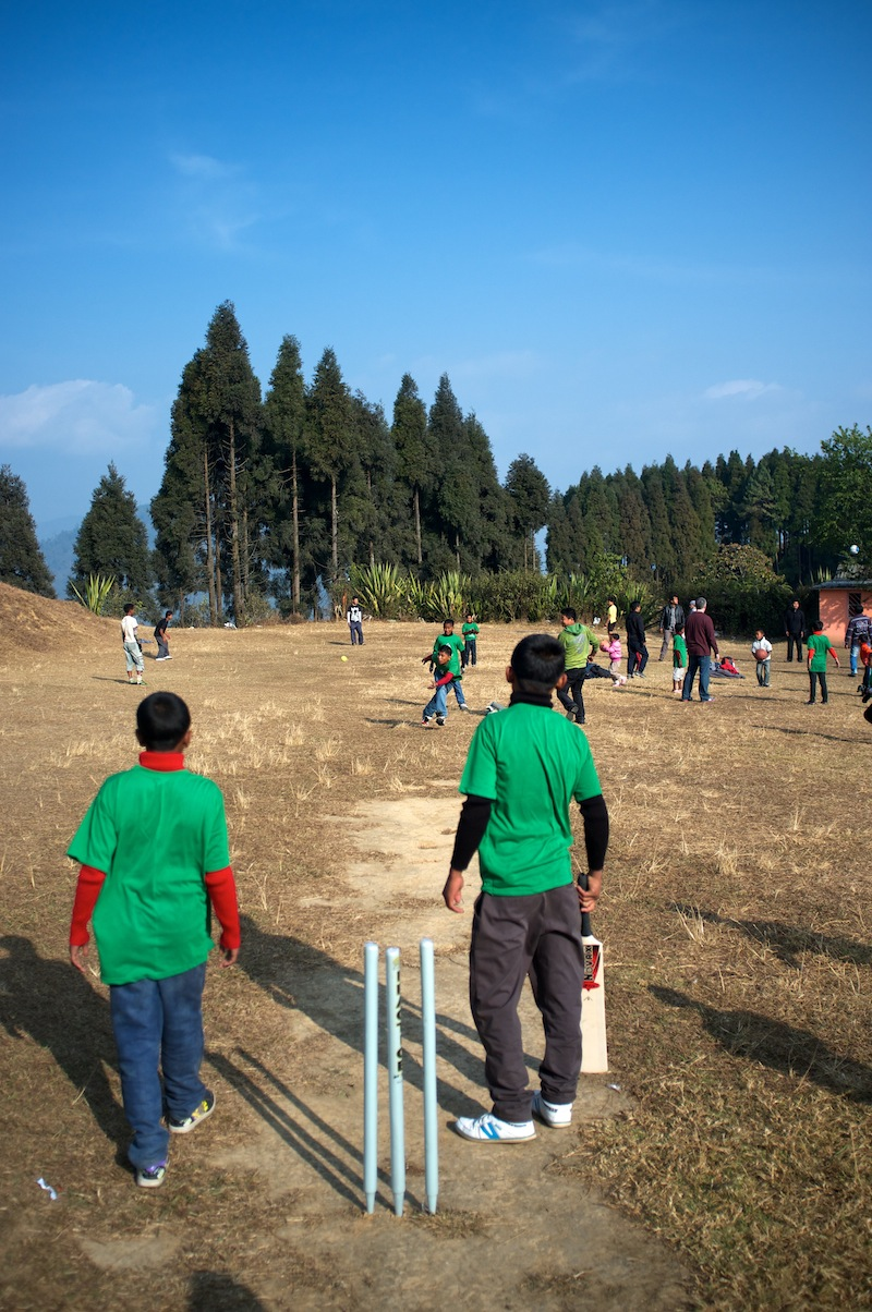The kids playing cricket at a park.