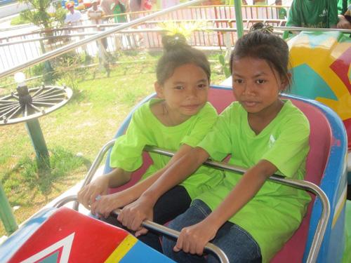 The kids riding rides at an amusement park.