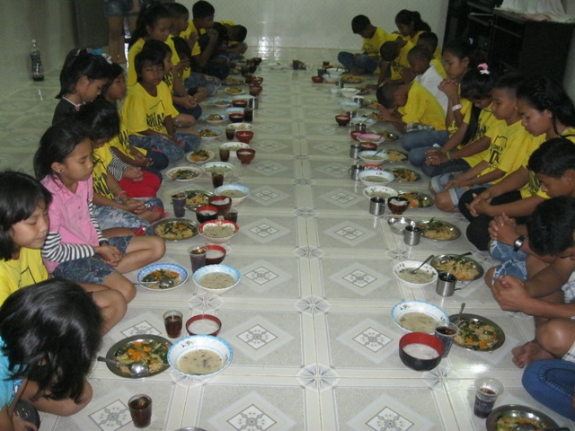 The kids say a prayer of thanks before enjoying a family meal.