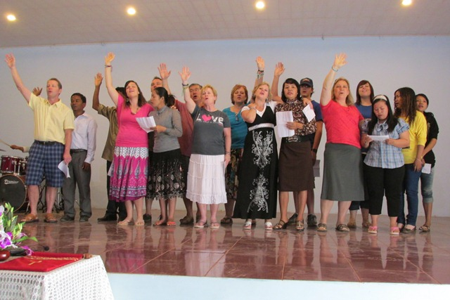 The team and the staff worship together at church.
