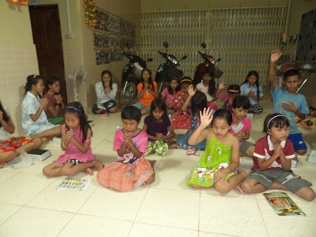 The kids gather to pray before studying.