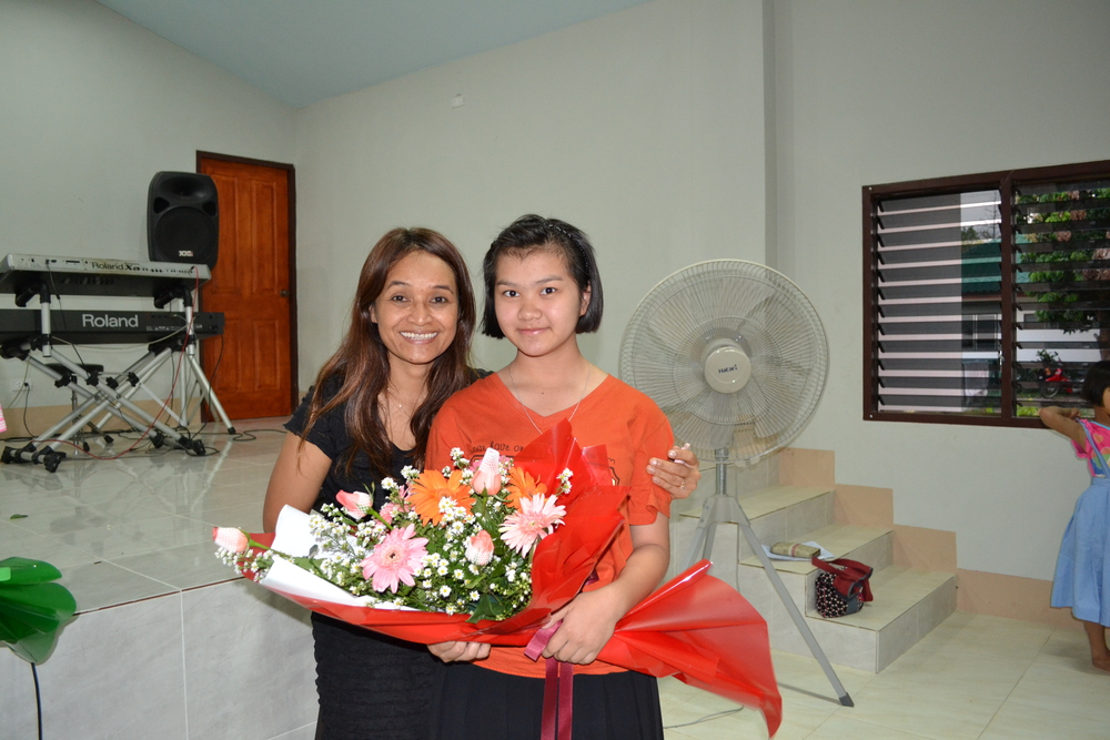 Tutu Bee, our Thailand national director presents bouquets to Asia's Hope students graduating from middle school.