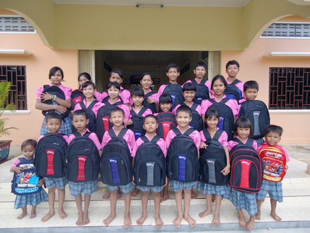 The children of Battambang 6 show off their new backpacks, gifts from the Crossroads Community Church in Mansfield, Ohio.