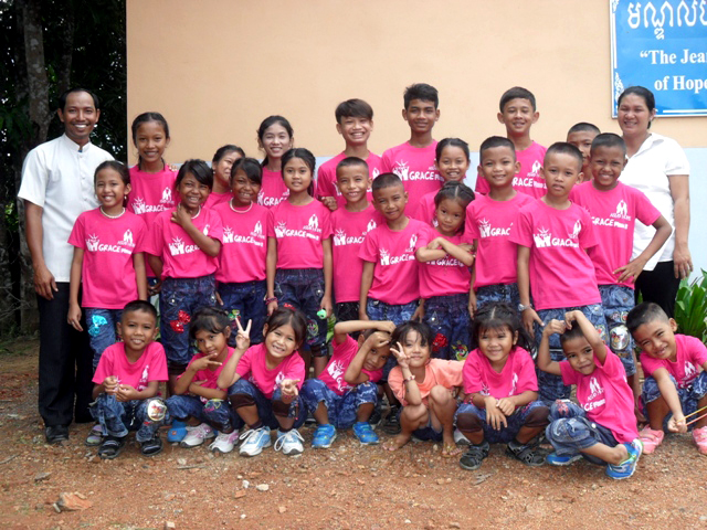 The kids and parents of Battambang 9 pose together as a family.