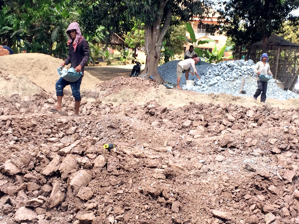In Cambodia, everything, even the mixing of concrete for the home's foundation, done by hand.