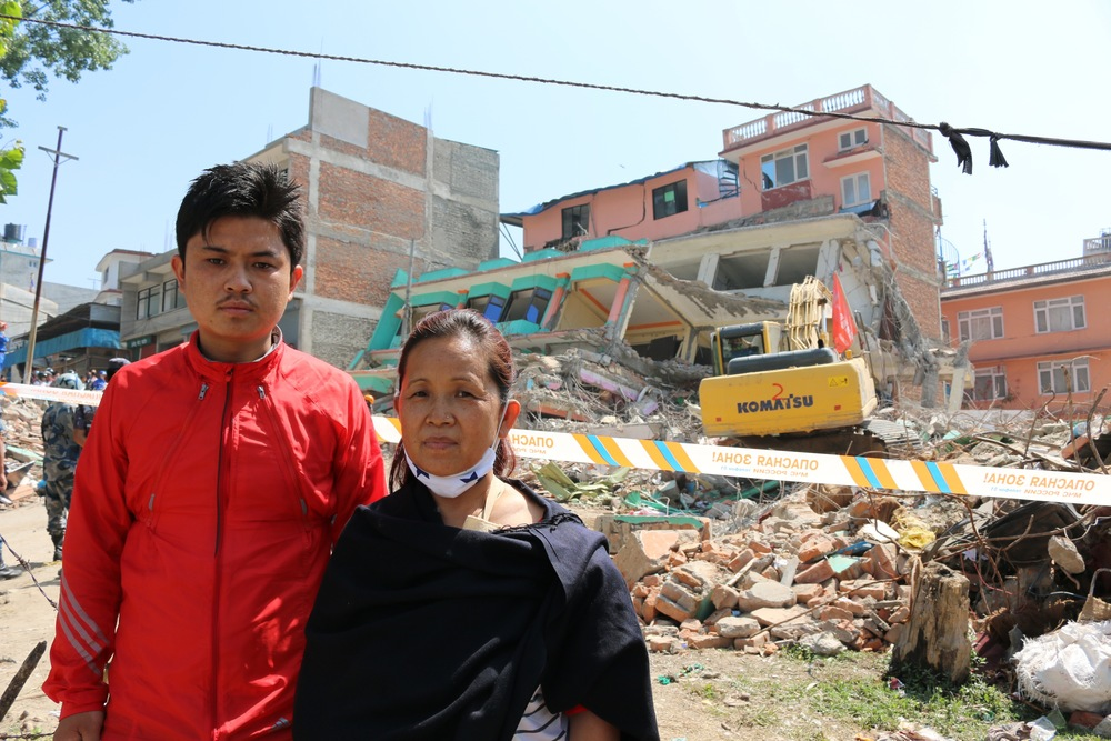 Biraj Ghale, youngest son of Pastor Elyia, and his mother stand in front of t he remains of their church which collapsed, trapping them inside.