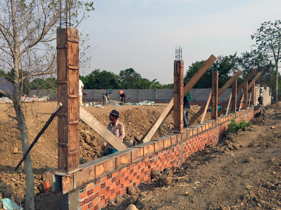 Masons continue on the boundary wall, even as work on the foundation begins.