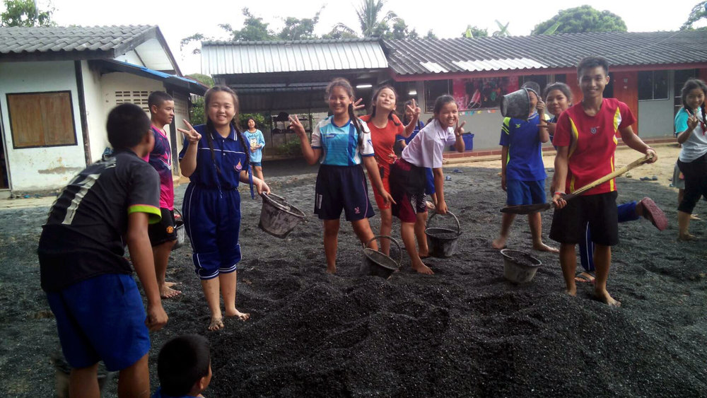 The kids are having a great time pitching in on a new concrete pad for the home!