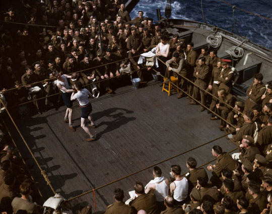 British soldiers watching a wrestling match on a troop ship from England to North Africa, 1943.